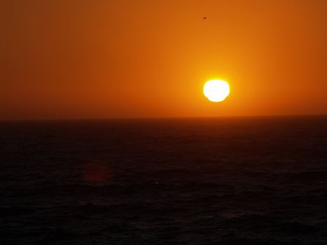 Sun setting over a dark ocean orange and black