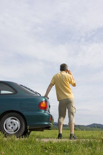 Man talking on cell phone beside his car which has a breakdown or a empty fuel tank