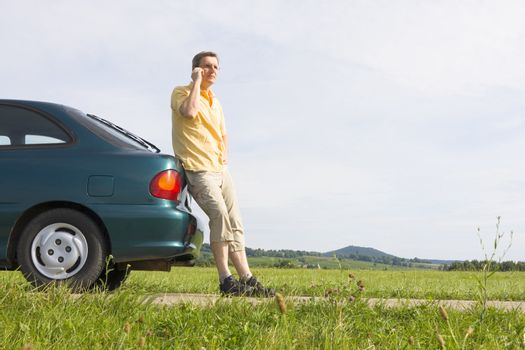 Man talking on cell phone beside his car which has a breakdown or a empty gas tank