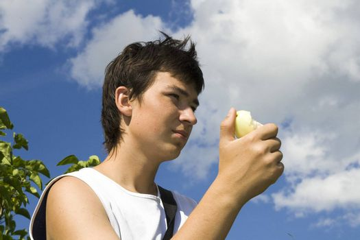 Young male eats apple with blue sky at background