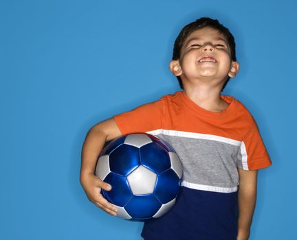 Male Hispanic boy holding soccer ball.