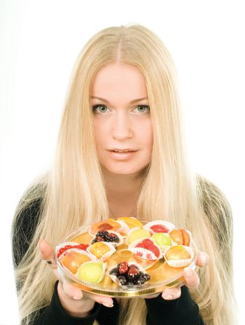 Attractive young woman with fruit candies over white background