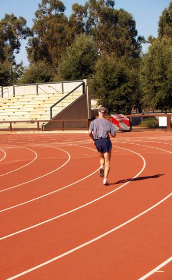 Man jogging at track taking curve outdoors