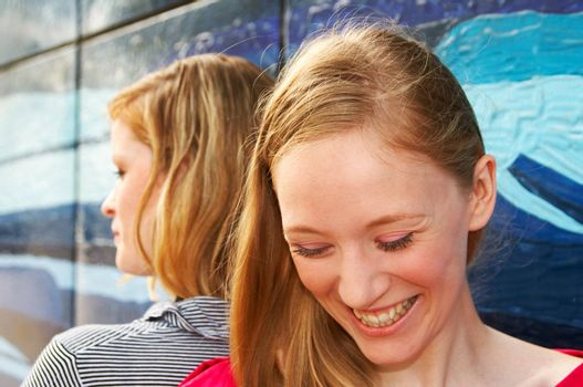 outdoor portrait of two laughing girls next to a painted wall