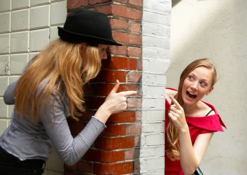 Two girls peeking around the two sides of the wall at house entrance