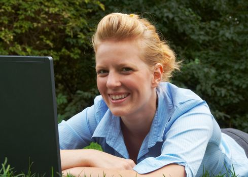 Smiling business woman lying on the grass in the park, working with laptop