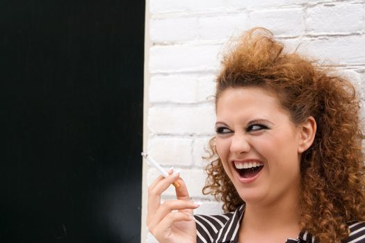 head portrait of a laughing gorgeous girl smoking cigarette; standing on a street next to painted brick wall