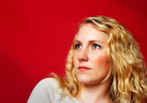 Portrait of a pretty blond girl on intense red background
