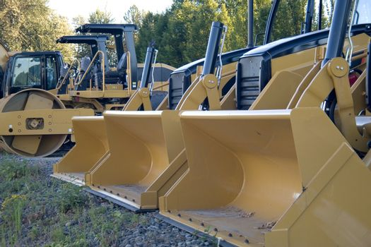 New yellow bulldozers in a row with buckets and rollers.