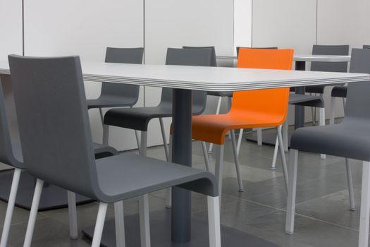Orange chair amongst grey chairs