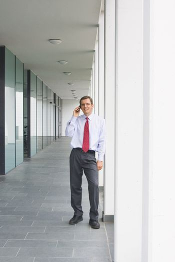 Businessman talking on mobile phone outside an office building