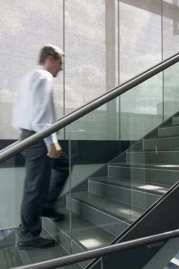 Motion blurred image of businessman climbing a stairway in an office building