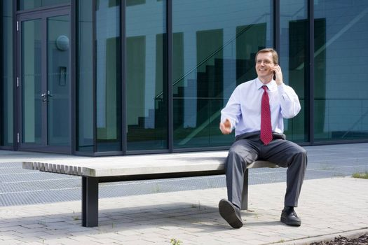 Businessman sitting on a bench in front of an office building and talking on mobile phone