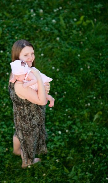 Happy young mother and her baby girl outdoors at sunny day