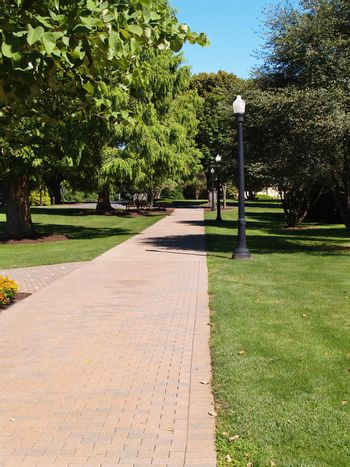 a brick walkway in a park setting
