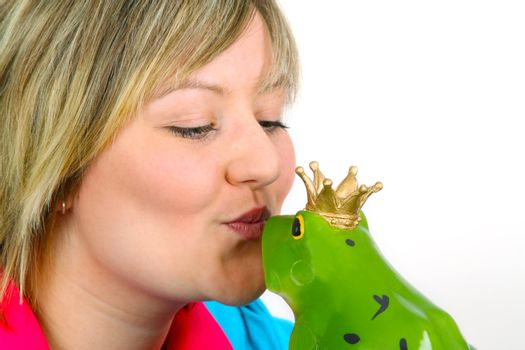 Young woman kissing a frog prince on white background. Shot in studio.