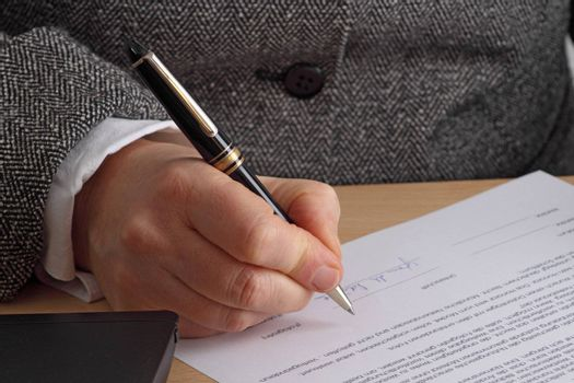 Hand with pen and contract. Shot in studio.