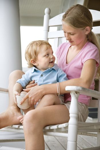 Caucasian pre-teen girl holding male Caucasian toddler looking at each other.