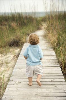 Little boy on beach walkway.