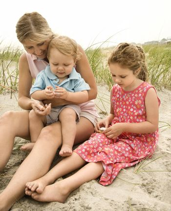 Mother and children looking at shells.