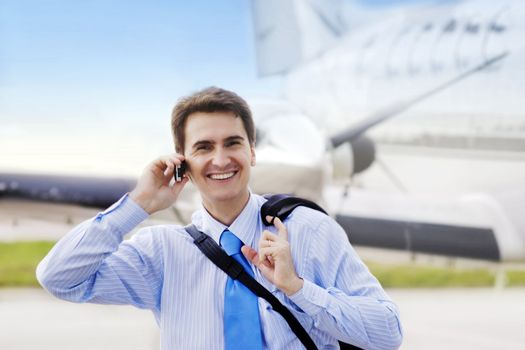 Businessman on airport with a mobile phone