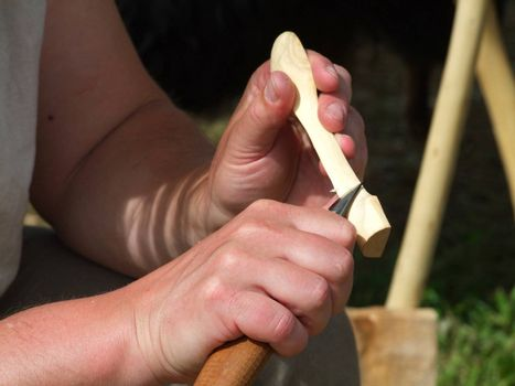 Hand in detail doing wood carving. Shot outdoor
