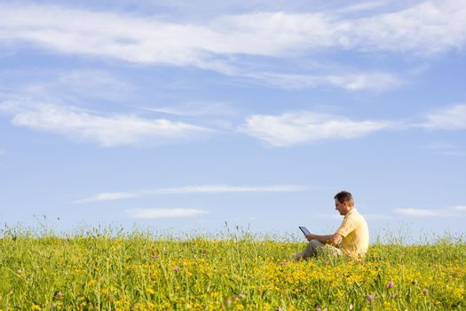 Man working with laptop in a meadow of flowers