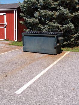 green garbage bin near a parking lot