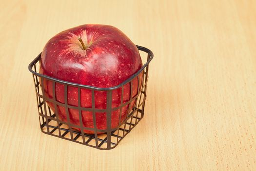 Red apple in a small basket