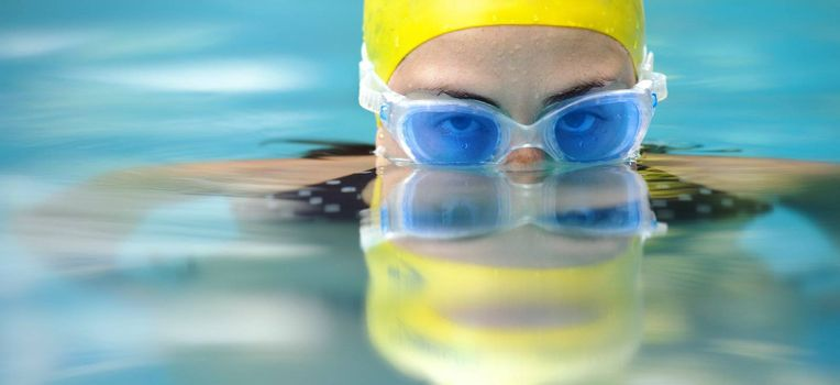 Girl is busy swimming and has blue goggles