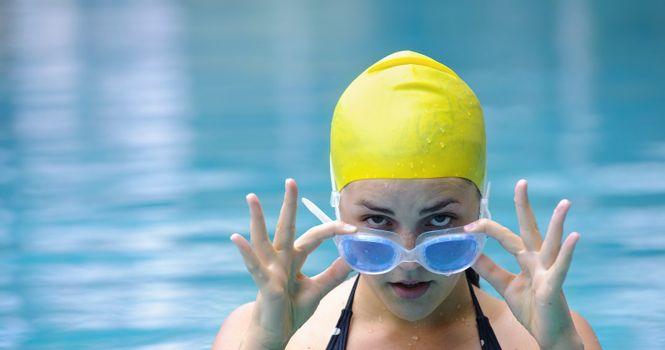 Female with goggles and swimming cap look toward camera