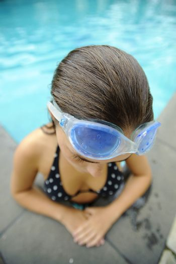 Girl takes a break from swimming at the pool edge