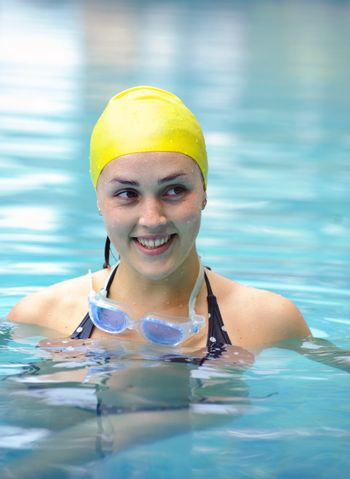 Female is happy in the pool with her cap and goggles