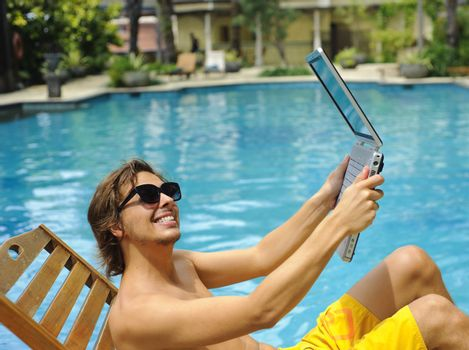 Man holds laptop up next to the pool