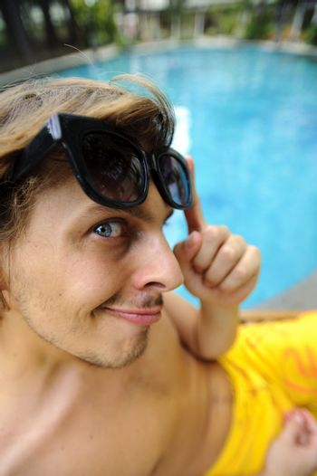 Tanning man looks at camera as he enjoys the hotel resort