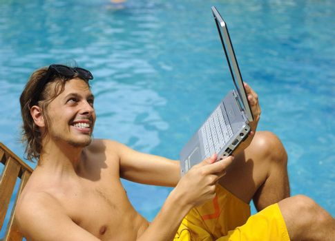 Attractive man uses his laptop while tanning poolside