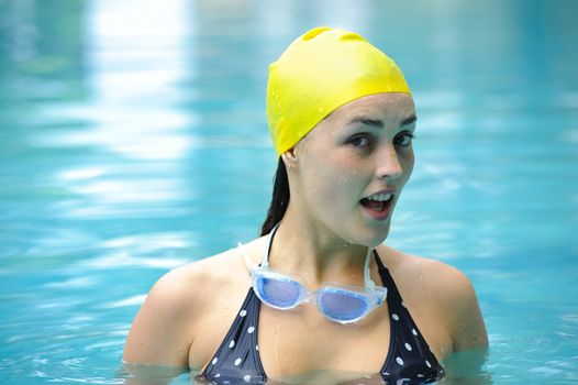 Female stands in the swimming pool with goggles