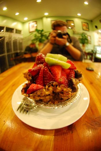 Person photographing a fruit tart