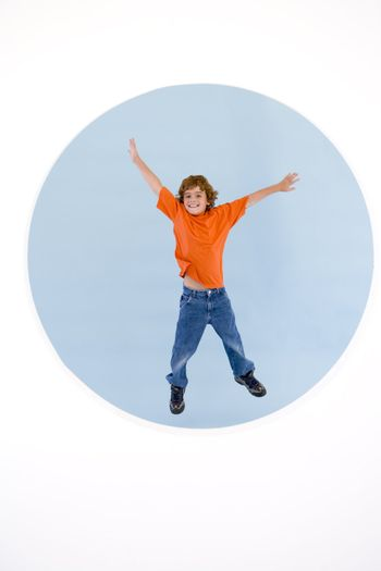 Young boy jumping with arms out smiling