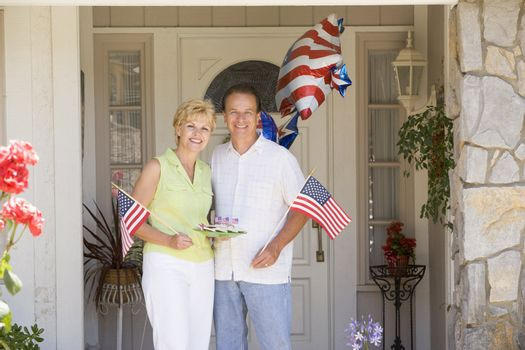 Couple at front door on fourth of July with flags and cookies sm