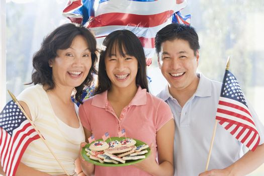 Family outdoors on fourth of July with flags and