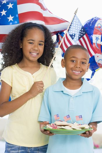 Brother and sister on fourth of July with flag and cookies smilie