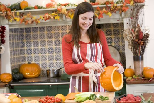 Woman carving jack o lantern on Halloween and smiling