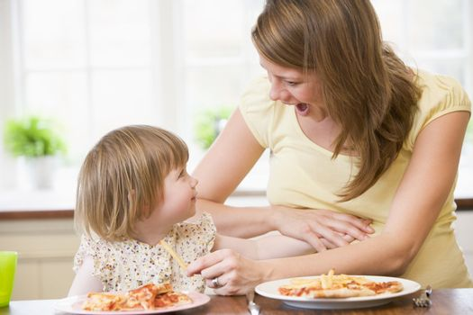 Pregnant mother with daughter touching belly eating French fries