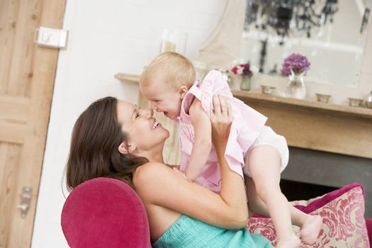 Pregnant mother in living room holding daughter and laughing