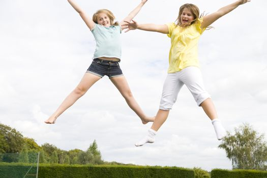 Two young girls jumping on trampoline smiling