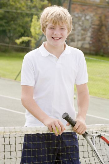 Young boy with racket on tennis court smiling