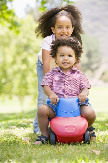 Sister pushing brother on toy with wheels smiling