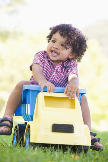 Young boy playing on toy dump truck outdoors