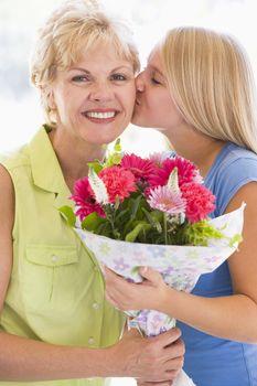 Granddaughter kissing grandmother on cheek holding